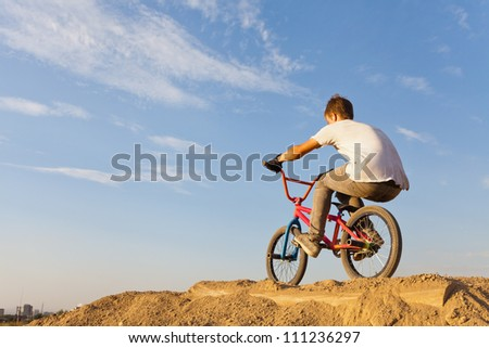 Image of teenager on a bicycle on a background blue sky. - stock photo