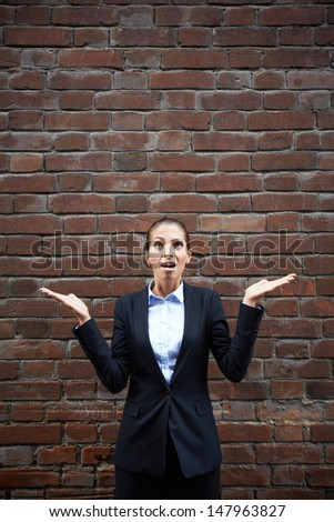 Image of terrified businesswoman with open palms on background of brick wall - stock photo