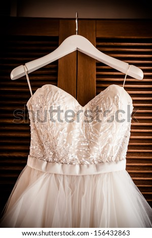 image of the bodice of a weeding dress on a hanger  against a wooden revolving door - stock photo
