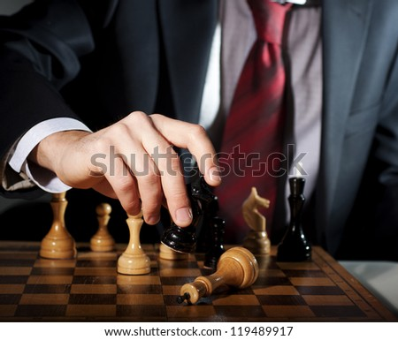 image of the businessman in a business suit plays chess - stock photo
