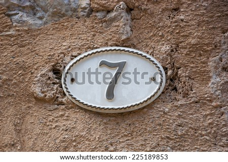 Image of the number 7 (indicating a house number) on weathered stucco wall of antique house. France. - stock photo