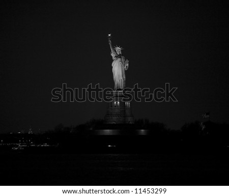 Image of the Statue of Liberty, on Ellis Island at night from the Staten Island ferry - stock photo