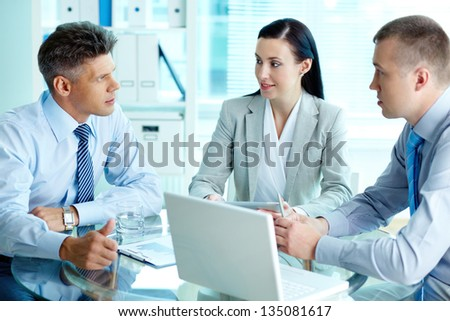 Image of three confident business partners interacting at meeting - stock photo