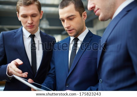 Image of three young businessmen discussing document in touchpad at meeting - stock photo