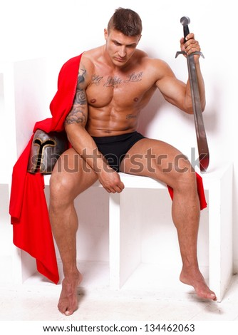 Image of topless warrior with red mantle who is bored - stock photo
