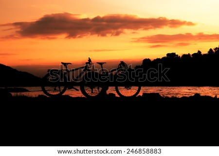 Image of two bicycles silhouetted against a dramatic sunset - stock photo
