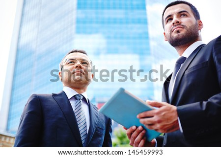 Image of two business guys in the urban environment, the younger one holding a touchpad - stock photo