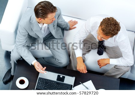 Image of two business partners discussing work at meeting - stock photo
