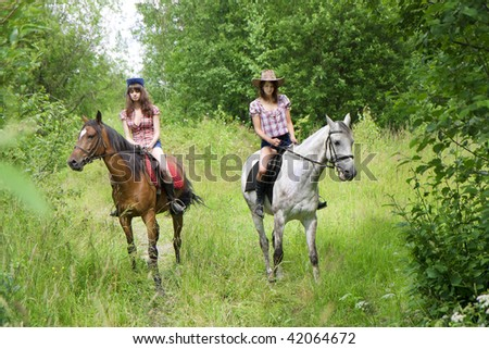 Image of two girls ride horses in the park - stock photo