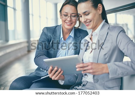 Image of two happy businesswomen discussing computer project - stock photo