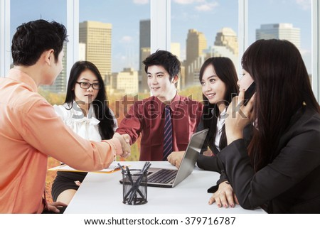 Image of two male entrepreneurs closing a business meeting by shaking hands in front of their partners at workplace - stock photo