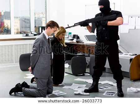 Image of two office workers standing on their knees in front of evil robber pointing gun at them - stock photo