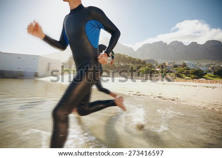 Image of two triathletes rushing into the water. Athlete running into the water, training for a triathlon. - stock photo