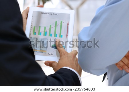 Image of two young businessmen using touchpad with graphs - stock photo