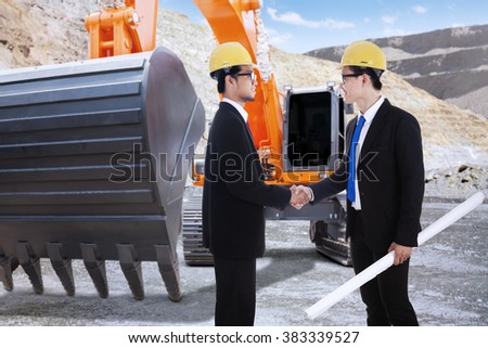 Image of two young engineer closing a deal by shaking hands near the excavator at the construction site - stock photo