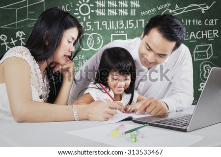 Image of two young parents helps a female student to write on the book in the classroom with laptop on desk - stock photo