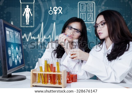 Image of two young researchers working with chemical liquid in the laboratory - stock photo