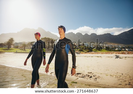 Image of two young triathletes walking into the sea wearing wetsuit. Man and woman doing triathlon training at the beach. - stock photo