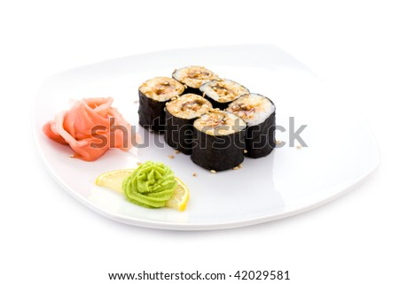 Image of unagi hosamaki sushi with sesame seeds, soy sauce, pickled ginger and wasabi on a plate - stock photo