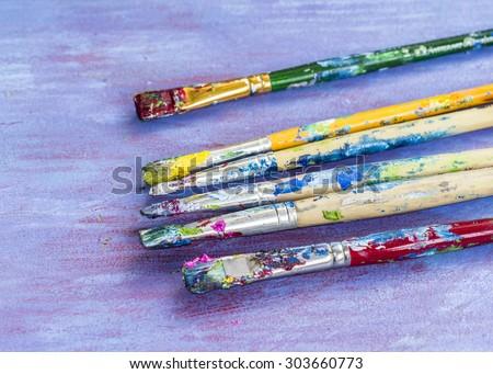 Image of used paint brush  on blue retro background - stock photo