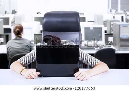 Image of very tired businesswoman with her face on keyboard of laptop. Shot at workplace - stock photo