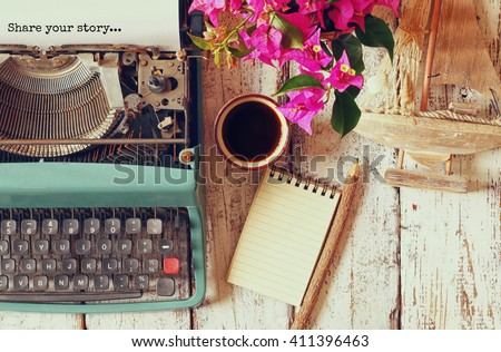 "image of vintage typewriter with phrase ""Share your story"", blank notebook, cup of coffee and old sailboat on wooden table - stock photo"