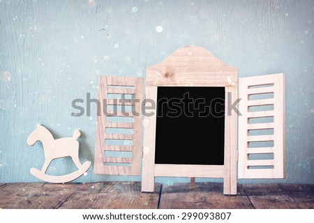 image of vintage wooden classical frame and wooden rocking horse on wooden table. filtered image with glitter overlay - stock photo