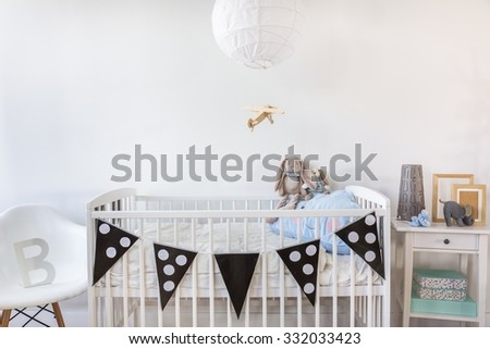 Image of white baby cot with decoration - stock photo