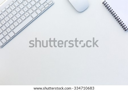 Image of White Office Desk with Computer Keyboard Mouse and Notepad from above - stock photo