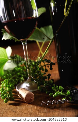 Image of wine goblet, bottle and cork on the wooden surface - stock photo