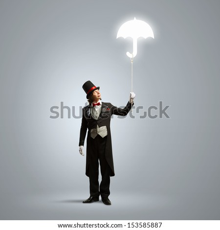 Image of wizard in hat holding umbrella - stock photo