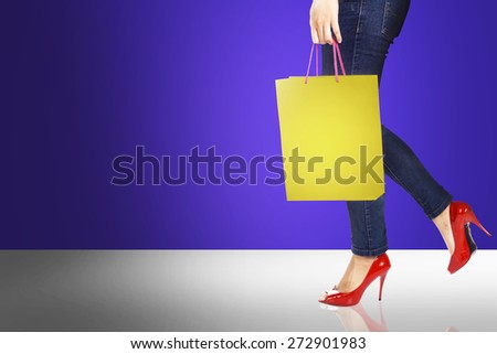 Image of woman leg wearing red shoes holding shopping bag - stock photo