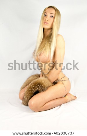 Image of woman's bare chest closeup portrait of a female sexy big breast / breast xxx / Beautiful slim body of woman in studio / hot sexy look blonde girl on white background, fox fur isolated closeup - stock photo
