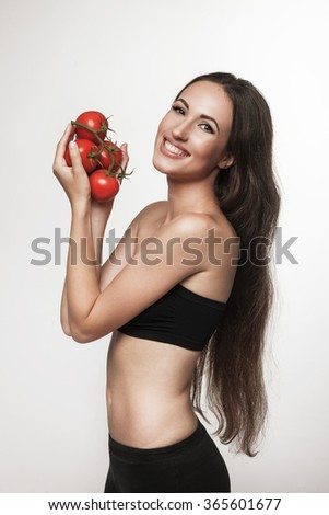 Image of woman showing tomatoes and smiling. Beautiful young brunette woman with slim body holding vegetables. Healthy eating and weight loss concept.  Studio white background. - stock photo