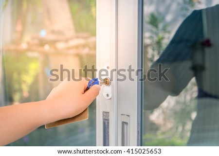Image of woman unlock or lock front door of house with key in hand. (soft focus) - stock photo