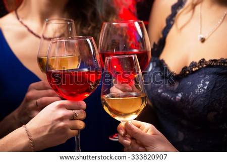 Image of women's hands with crystal glasses of wine - stock photo