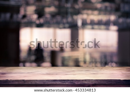 image of wooden table in front of abstract blurred background of restaurant lights, use for product display mock up.  - stock photo