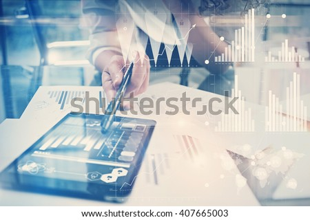 Image of working process. Finance director work new global project in worldwide bank office. Using modern tablet. Graphics icons, tax, stock exchanges interface. Horizontal - stock photo