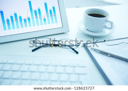 Image of workplace with electronic document, cup of coffee and eyeglasses on it - stock photo
