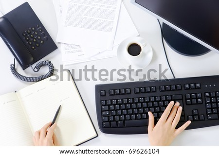 Image of workplace with office objects and female hands - stock photo