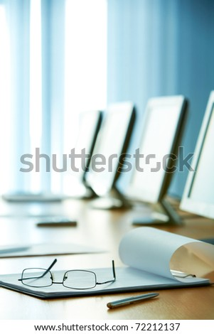 Image of workplace with paper, eyeglasses and monitors near by - stock photo