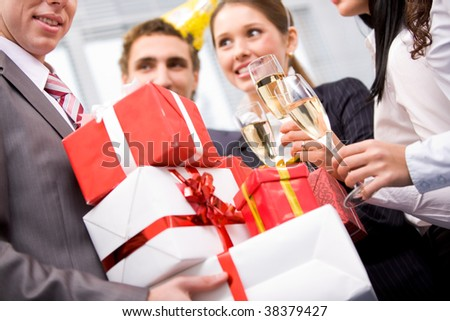 Image of wrapped giftboxes in male hands with cheering friends on background - stock photo