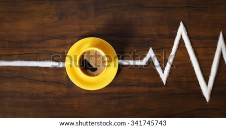 Image of yellow coffee cup and saucer on table with sugar lane in shape of heartbeat cardiogram - stock photo