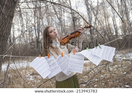 Image of young adult  girl in winter cold park with dry grass and snow playing with her violin near paper notes Copy space for inscription - stock photo