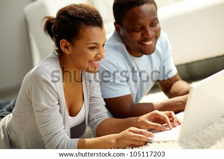 Image of young African couple networking at home - stock photo
