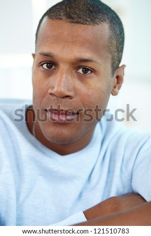 Image of young African man looking at camera with calm expression - stock photo