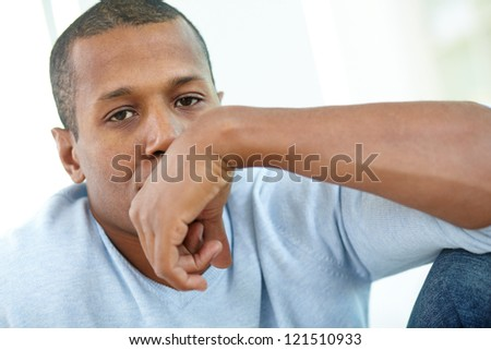 Image of young African man looking at camera with hand by his face - stock photo