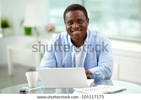 Image of young African man looking at camera with laptop near by - stock photo