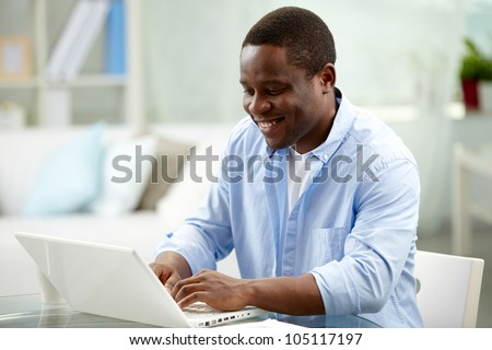 Image of young African man typing on laptop - stock photo