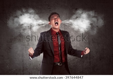 Image of young asian businessman in anger. Smoke out from his ears - stock photo